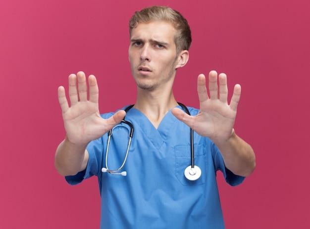 Strenger junger männlicher arzt, der arztuniform mit stethoskop trägt, hält hände an der kamera lokalisiert auf rosa wand