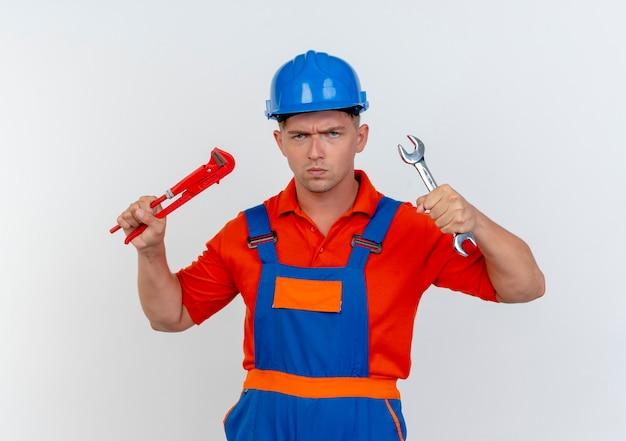 Strenger junger männlicher baumeister, der uniform und schutzhelm hält schlüssel auf weiß hält