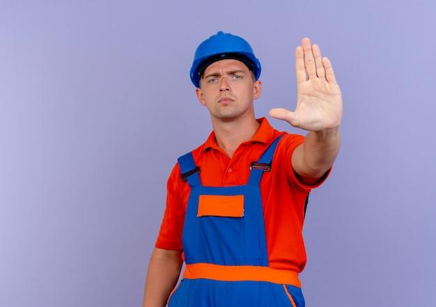 Strenger junger männlicher baumeister, der uniform und schutzhelm trägt, der stoppgeste zeigt