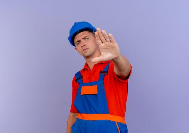Strenger junger männlicher baumeister, der uniform und schutzhelm trägt und stoppgeste auf purpur zeigt