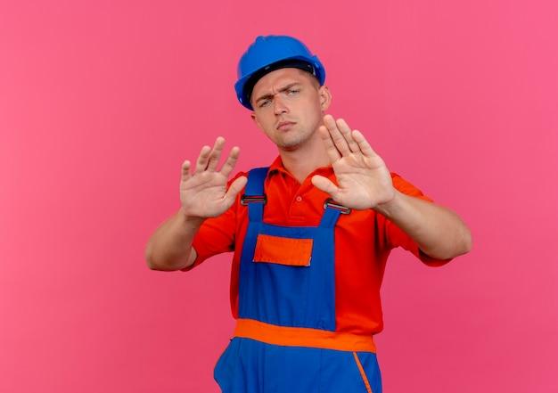 Strenger junger männlicher baumeister, der uniform und schutzhelm trägt und stoppgeste auf rosa zeigt