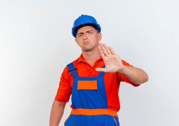 Strenger junger männlicher baumeister, der uniform und schutzhelm trägt und stoppgeste auf weiß zeigt