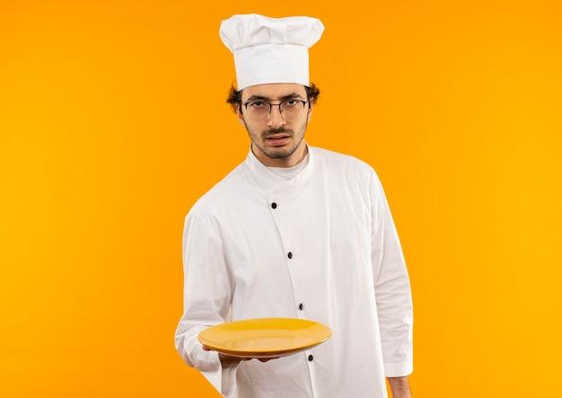 Strenger junger männlicher koch, der kochuniform und brille hält platte trägt, die auf gelber wand lokalisiert werden