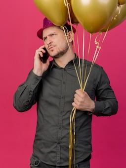 Strenger junger party-typ, der rosa hut hält, der luftballons hält und am telefon isoliert auf rosa spricht