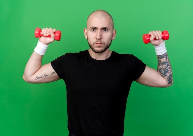 Strenger junger sportlicher mann, der armband trägt, das mit hantel auf grün lokalisiert trainiert