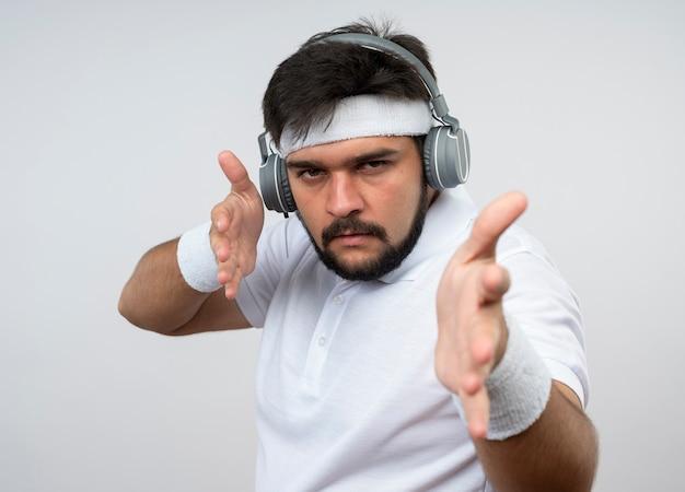 Strenger junger sportlicher mann, der stirnband und armband mit kopfhörern trägt, die hände lokalisiert auf weißer wand halten