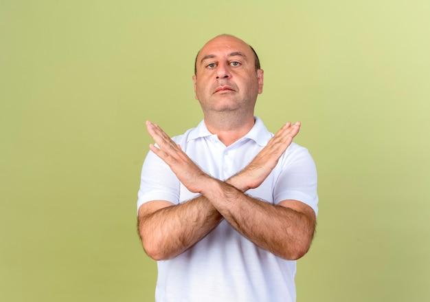 Strenger reifer mann, der geste des nicht-isolierten auf olivgrüner wand zeigt