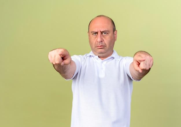 Strenger reifer mann, der sie geste lokalisiert auf olivgrüner wand zeigt