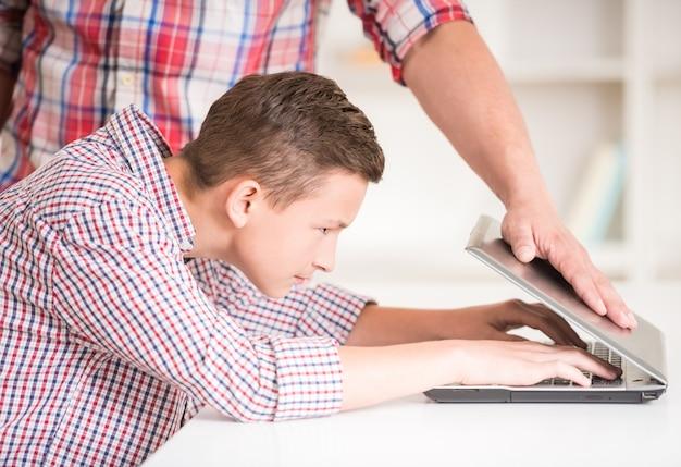 Strenger vater, der versucht, laptop seines sohns zu schließen.
