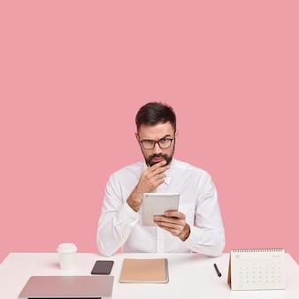 Strenger verwaltungsmanager checkt e-mails auf dem touchpad, genießt seinen beruf und trägt formelle kleidung