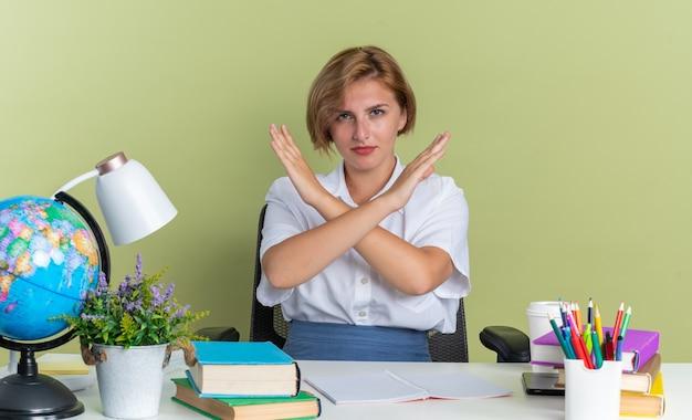 Strenges junges blondes studentenmädchen, das am schreibtisch mit schulwerkzeugen sitzt und keine geste macht