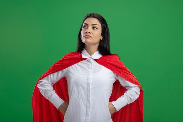 Strenges junges kaukasisches superheldenmädchen, das hände auf hüften hält, die gerade lokal auf grünem hintergrund mit kopienraum suchen