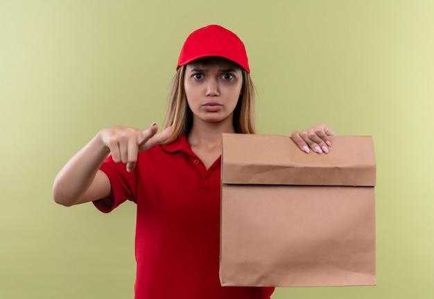 Strenges junges liefermädchen, das rote uniform und kappe hält, die papiertüte hält und sie geste lokalisiert grün zeigt
