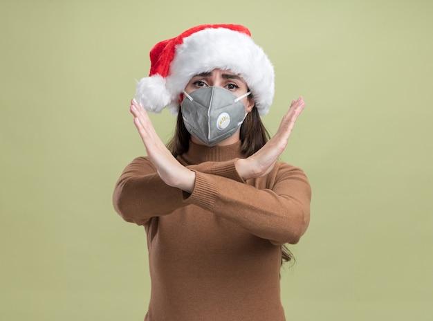 Strenges junges schönes mädchen, das weihnachtsmütze mit medizinischer maske trägt, die geste von nicht isoliert auf olivgrünem hintergrund zeigt