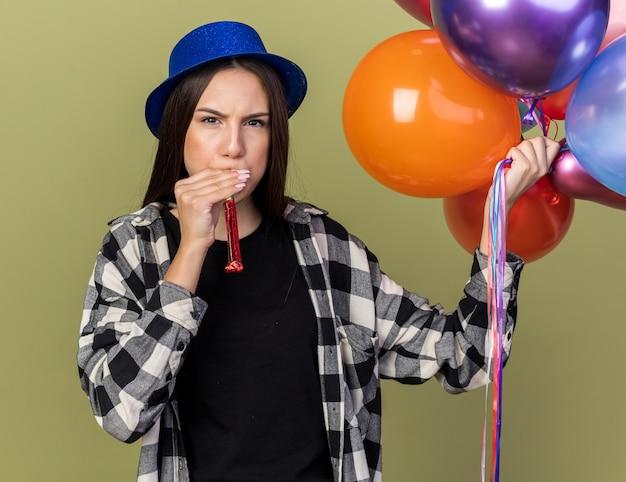 Strenges junges schönes mädchen mit blauem hut mit luftballons, die partypfeife blasen