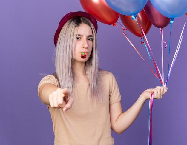 Strenges junges, schönes mädchen mit partyhut, das luftballons hält und die partypfeife bläst, die ihnen geste isoliert auf blauer wand zeigt