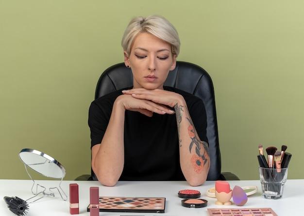 Strenges junges schönes mädchen sitzt am tisch mit make-up-tools, die die hand unter dem kinn halten, isoliert auf olivgrünem hintergrund