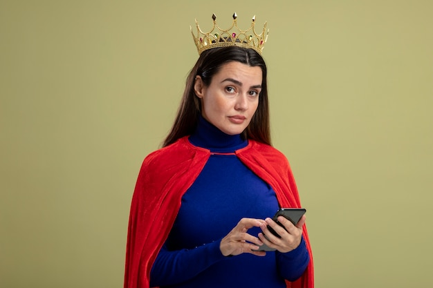 Strenges junges superheldenmädchen, das krone hält telefon lokalisiert auf olivgrün trägt