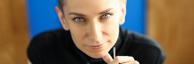 Strenges weibliches porträt im büro, das in kamera schaut