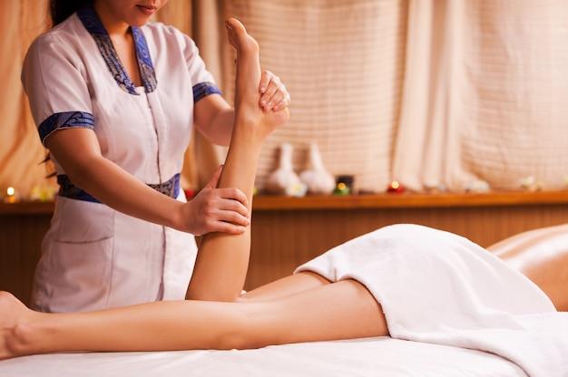 Stress abbauen. draufsicht des massagetherapeuten, der schönes weibliches bein massiert