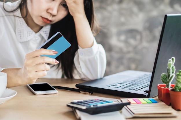 Stress asiatische frau, die in der hand kreditkarte betrachtet