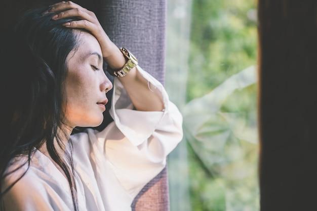 Stress asiatische frau mit kopfschmerzen neben dem fenster