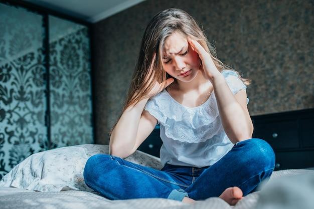 Stress frau mit migräne. kopfschmerzen, die ihren kopf vor schmerz und stress halten.