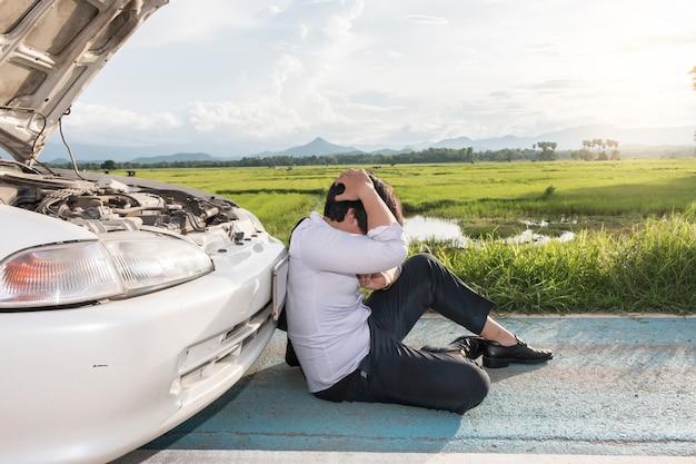 Stress mann sitzt auf einem kaputten auto