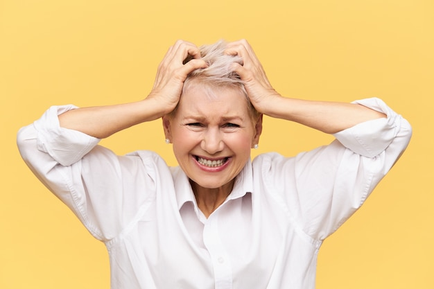 Stress, probleme, wut, wut und negative emotionen. frustrierte verzweifelte reife frau, die schreit und haare abreißt, wütend auf versagen ist, gestresst von finanziellen problemen und die beherrschung verliert