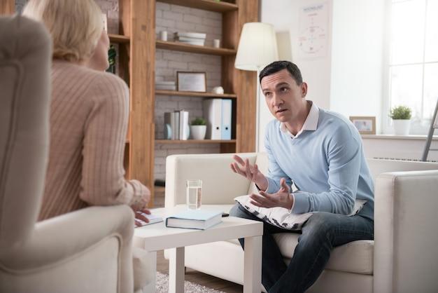 Stressbewältigung. unbehaglicher verärgerter mann, der beim gestikulieren auf der couch sitzt