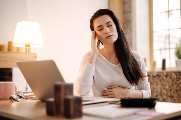 Stressige arbeit. traurige unglückliche schwangere geschäftsfrau, die augen schließt, die schläfe massiert und von der arbeit zu hause ruht