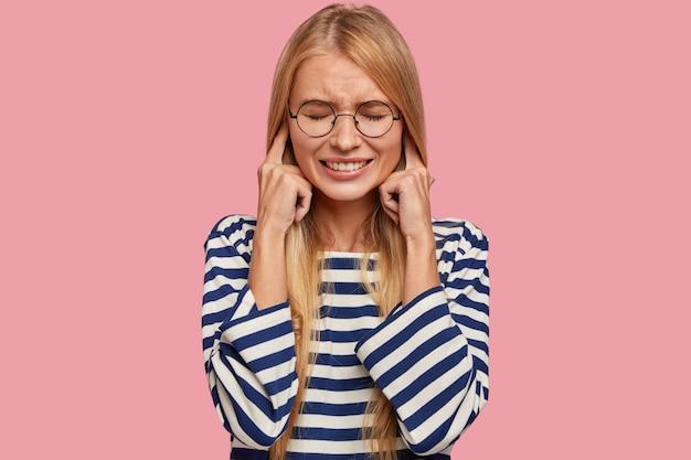 Stressige blonde frau stopft ohren, macht schiefes gesicht, ignoriert unangenehme geräusche
