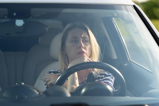 Stressige fahrerin hat angst vor dem autofahren nach einem autounfall unglückliche dame, die angst vor straße und verkehr hat