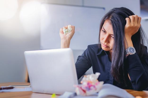 Stressige geschäftsfrau, die im büro müde und gelangweilt arbeitet.