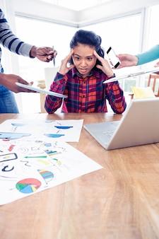 Stressige junge geschäftsfrau, die unten beim sitzen im kreativen büro schaut