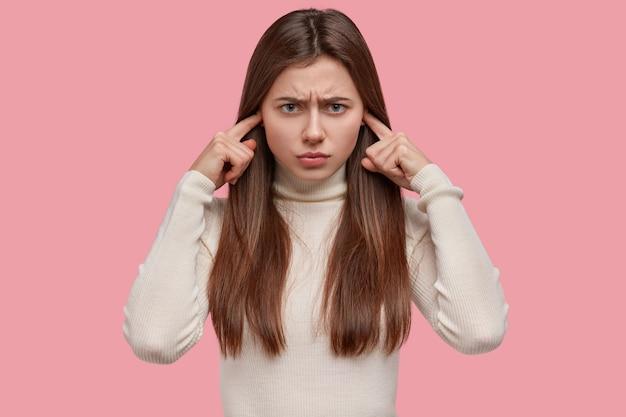 Stressige unglückliche kaukasische dame ignoriert etwas unangenehmes, verstopft die ohren, ärgert sich über lautes geräusch, runzelt die stirn, hat einen düsteren ausdruck