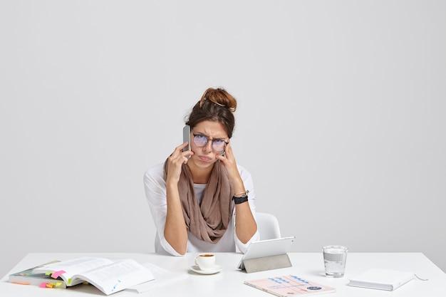 Stressige unternehmerin kommuniziert per handy während der arbeit am digitalen tablet