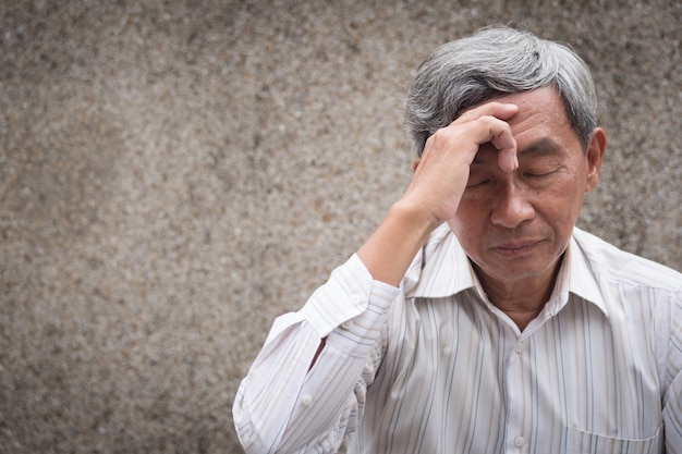Stressiger älterer alter mann, der unter kopfschmerzen leidet