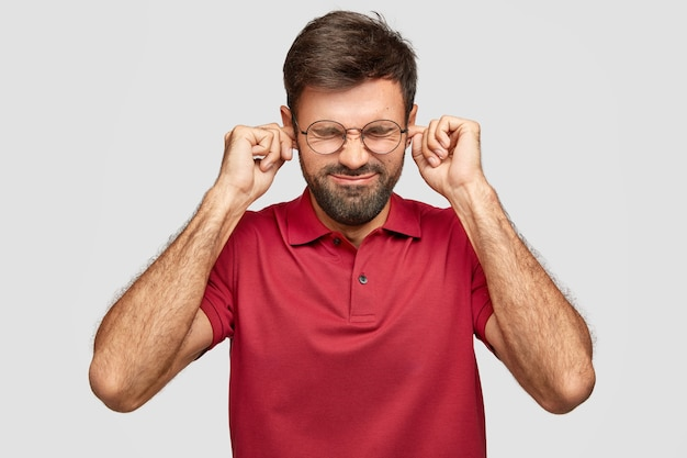 Stressiger bärtiger kaukasischer mann stopft ohren mit fingern, hält augen geschlossen