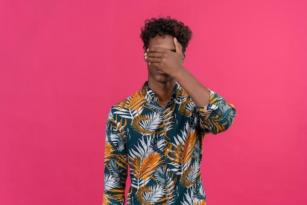 Stressiger junger gutaussehender dunkelhäutiger mann mit lockigem haar im bedruckten hemd der blätter, das augen mit handfläche auf einem rosa hintergrund bedeckt