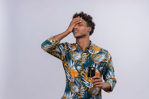 Stressiger junger gutaussehender dunkelhäutiger mann mit lockigem haar im bedruckten hemd der blätter, das kreditkarte zeigt, während augen geschlossen gehalten werden, die stirn mit handfläche auf einem weißen hintergrund berühren