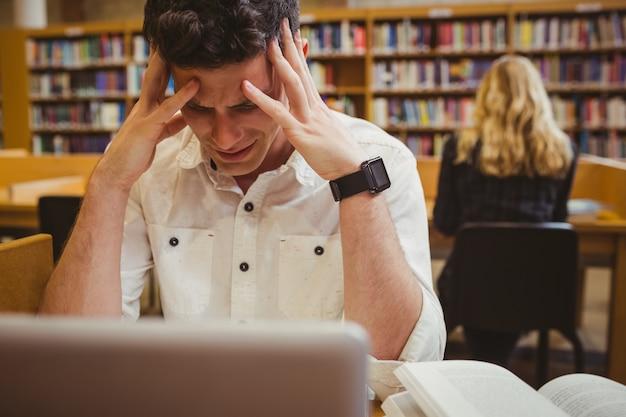 Stressiger student, der seinen kopf in der bibliothek hält