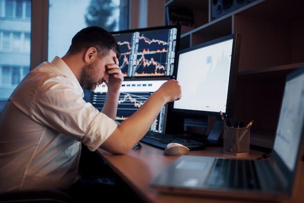 Stressiger tag im büro. händchenhalten des jungen geschäftsmannes auf seinem gesicht beim sitzen am schreibtisch im kreativen büro. börse, die devisen-finanzgraphik handelt