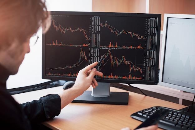 Stressiger tag im büro. händchenhalten des jungen geschäftsmannes auf seinem gesicht beim sitzen am schreibtisch im kreativen büro. börse, die devisen-finanzgraphik-konzept handelt