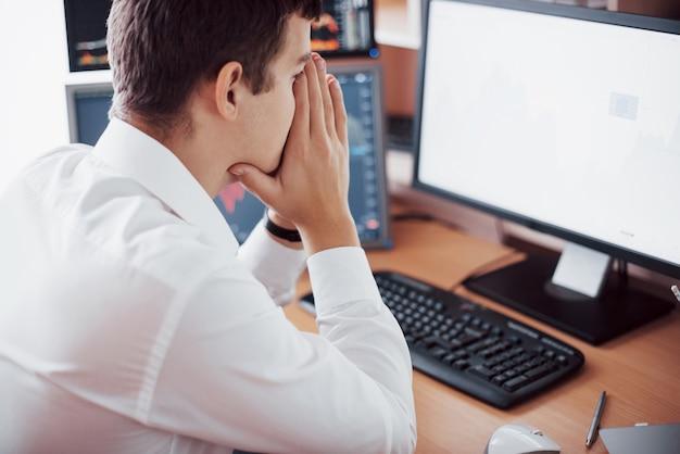 Stressiger tag im büro. junger geschäftsmann, der hände auf seinem gesicht hält, während er am schreibtisch im kreativen büro sitzt. börsenhandel forex finance grafikkonzept