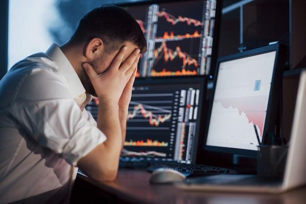 Stressiger tag im büro. junger geschäftsmann, der hände auf seinem gesicht hält, während er am schreibtisch im kreativen büro sitzt. börsenhandel forex finance grafikkonzept.