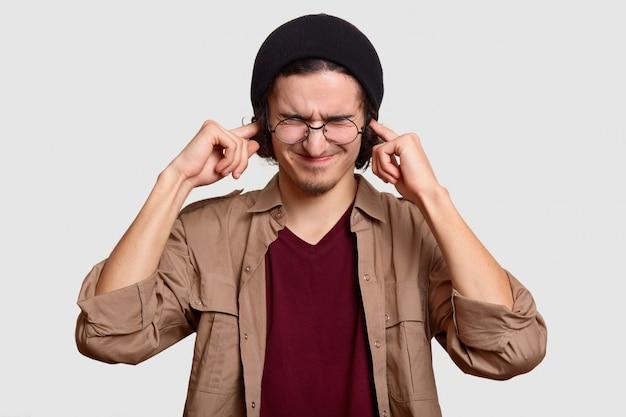 Stressiger teenager trägt schwarzes har und beige hemd, stopft ohren, ignoriert laute geräusche von lärmnachbarn, steht auf weiß. frustrierter hipster, der sich über etwas lautes ärgert
