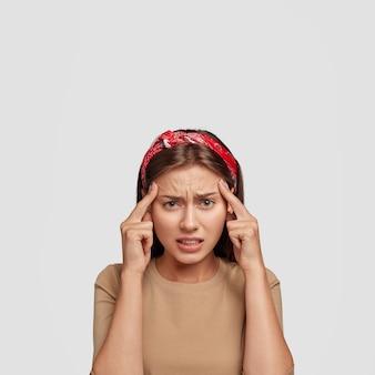 Stressiger unzufriedener junger student, der gegen die weiße wand aufwirft