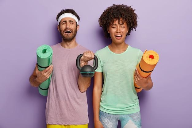 Stressiges, abwechslungsreiches paar fühlt sich nach dem sporttraining mit dem trainer müde, hält fitnessmatten, gewicht