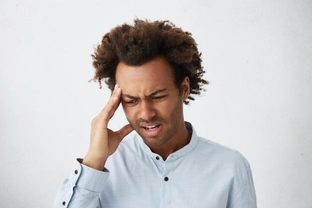 Stressvoller afroamerikanischer mann mit buschigem haar, das sein gesicht runzelt, das hand auf schläfe hält
